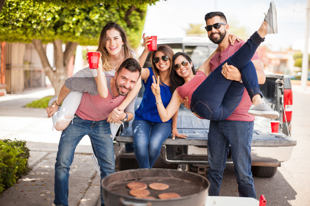 hanging woman: Group of young attractive friends tailgating, drinking beer and having some fun together next to a grill