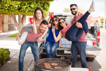 Gruppe der jungen attraktiven Freunden dichtes Auffahren, Bier zu trinken und Spaß zusammen neben einem Grill mit