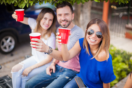 good weather: Group of happy friends drinking beer in plastic cups and watching a sports game together at a barbecue