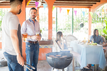 Two handsome yoyng men grilling hamburgers for their friends and drinking beer in the backyard Stockfoto