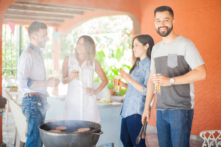 Handsome young Latin man cooking some hamburgers with his friends and drinking beer at a reunion and smiling Stock Photo