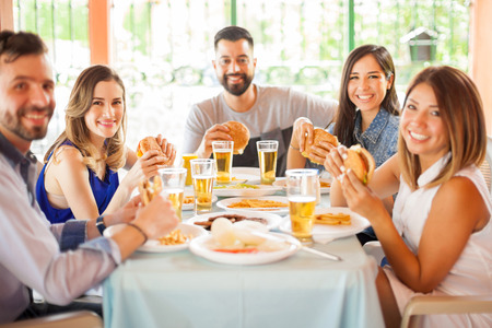Good looking friends sitting together at a table, eating burgers and having fun during a barbecue in a patio Stock Photo