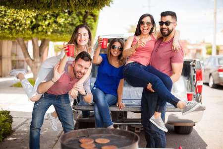 young friends: Group of good looking Hispanic friends drinking beer and having some fun together at a barbecue