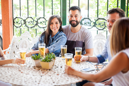 Portrait of a young Latin couple drinking some beer and having a good time with their friends outdoors Stock Photo