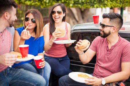 4 명의 좋은 찾고 히스패닉 친구들이 재미있는 동안 치즈 버거를 먹고 바베큐 파티 야외에서 맥주를 마시는 중