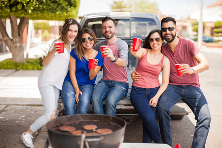 Hispanic friends sitting in the back of a pick up truck and tailgating while drinking cold beers outside