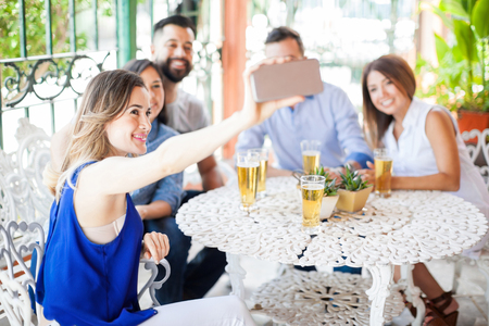 Five youn good looking Latin friends taking a selfie with a smartphone during a barbecue outdoors
