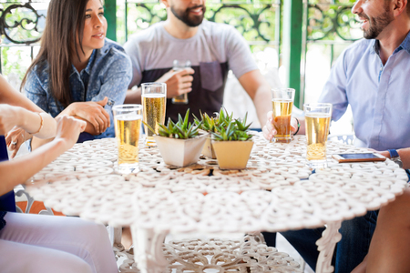 Closeup of a group of friends passing the time and drinking cold beers in a deck outdoors Stock Photo