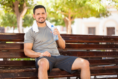 eye shade: Portrait of a happy young man drinking some water from a bottle while sitting and resting in a park bench after doing some jogging outdoors Stock Photo