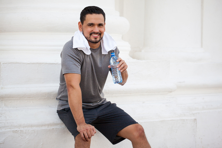 Attractive male runner drinking water from a bottle and cooling down after working out in the city
