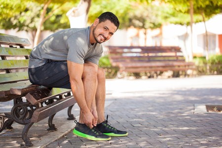 Portrait of a handsome Hispanic young man getting ready to go running at a park and smiling