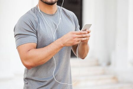 earbuds: Closeup of a young man in sporty outfit listening to music with his smartphone and earbuds before exercising outdoors