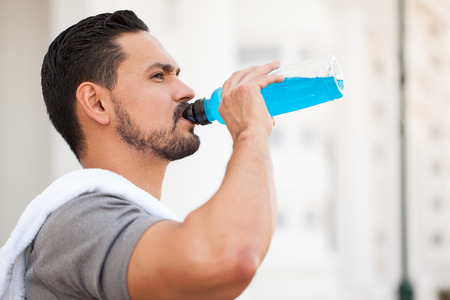 Closeup of a handsome young man with a beard drinking a sports drink from a bottle after running outdoors in the city