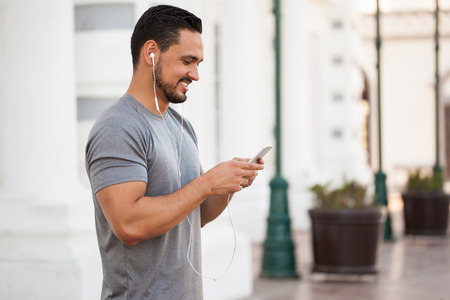 earbuds: Profile view of a male runner wearing earbuds and selecting the right playlist on a smartphone for his training Stock Photo
