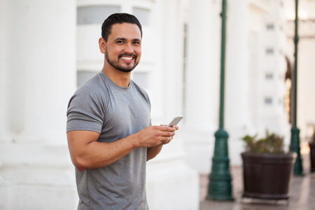 Portrait of a good looking young Hispanic man with a beard and sporty outfit using a smartphone before going for a run in the city