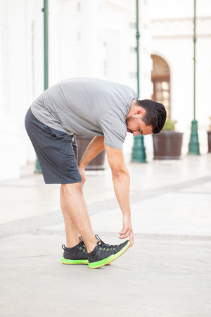touching toes: Young man in sporty outfit stretching and reaching for his toes before going for a run in the city