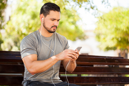 earbuds: Closeup of a handsome young man listening to music from his smartphone using earbuds while sitting in a park bench