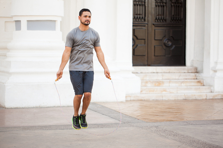 saltar la cuerda: Retrato de cuerpo entero de un joven atl�tico usando una cuerda para saltar al ejercicio al aire libre