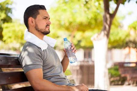 Closeup of a handsome young man drinking water from a bottle while taking a break from working out in a park