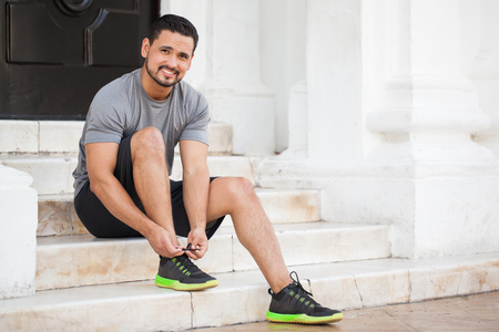 Handsome young Latin man tying his shoes and getting ready to workout and go for a run outdoors in the city