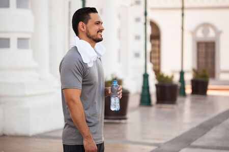 cool down: Profile view of a handsome young man taking a break from exercising in the city and drinking water to cool down