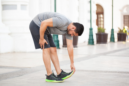 touching toes: Profile view of a good looking young man stretching and touching his toes before going jogging in the city Stock Photo