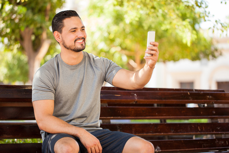 uomini belli: Attractive young man with sporty outfit taking a selfie while sitting in a park bench before exercising outdoors Archivio Fotografico
