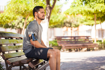 earbuds: Profile view of a good looking young man working out at a park and taking a break while listening to music with earbuds and a smartphone