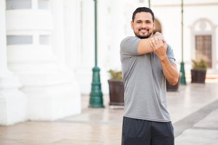 Portrait of a happy Hispanic young runner stretching his arms before working out in the city