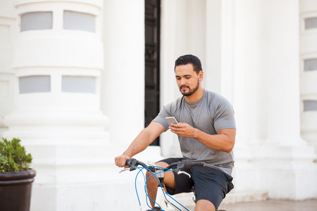 distracted: Young man getting distracted by his smartphone while riding his bicycle around the city