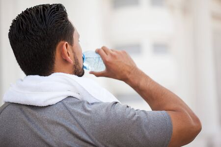 Rear view of a young man drinking water from a bottle after running and exercising outdoors Stock Photo