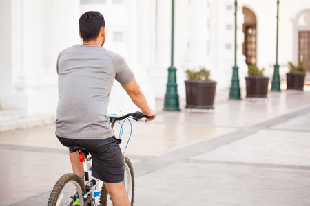 man behind: Athletic young man wearing shorts and riding a bicycle around the city, seen from behind Stock Photo