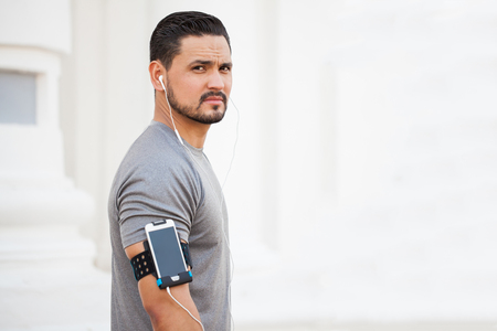 earbuds: Attractive young man listening to music with earbuds and a smartphone in an armband while exercising outdoors Stock Photo