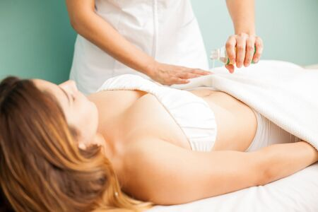 drainage: Female therapist pouring some massage oils on a client before giving her a lymphatic massage at a spa