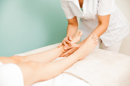 masseuse: Closeup of a female masseuse giving a foot massage to one or her clients at a health and beauty spa