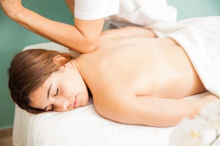 Entspannt junge Frau, die eine Tiefenmassage von einem weiblichen Therapeuten in einer Klinik bekommen, aus der Nähe gesehen