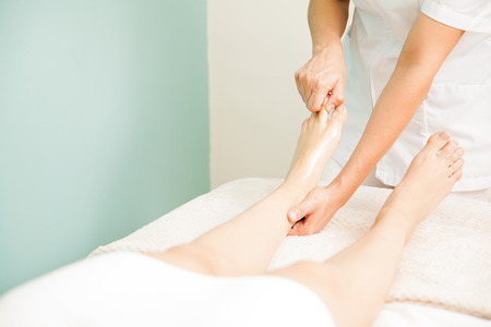 masseuse: Close up of a masseuse giving a foot massage to a client at a spa. Plenty of copy space