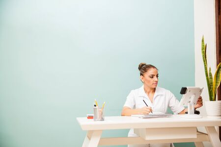front desk: Portrait of a pretty therapist working at a health and beauty clinic and spa taking notes in a front desk Stock Photo