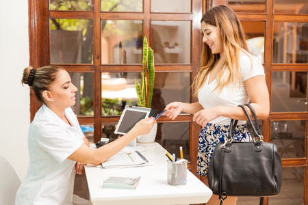 Cute young woman using a credit card to pay for a massage at a health and beauty spa and smiling Reklamní fotografie - 60090479
