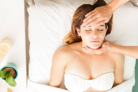holistic view: Beautiful young woman relaxing at a reiki session in a health and beauty spa, her therapist with hands on forehead, seen from above
