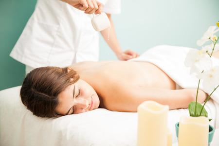 Velmi uvolněná a roztomilá mladá žena získává masáž svíčky v kosmetických salonech a lázních Reklamní fotografie