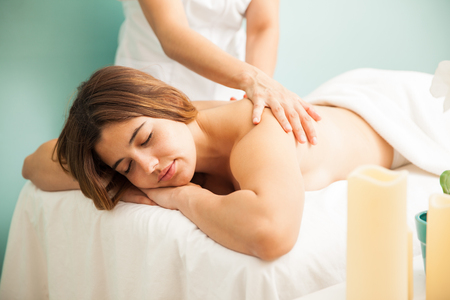 masseuse: Beautiful young Hispanic woman falling asleep as a masseuse gives her a very relaxing massage at a spa