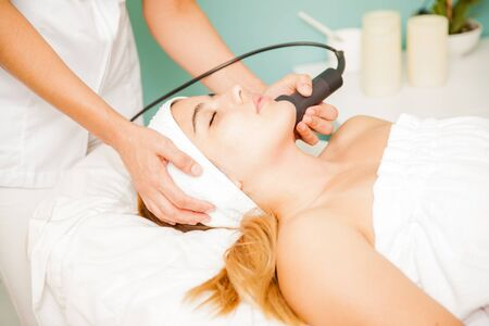 health beauty: Profile view of a young brunette in a facial therapy session at a health and beauty spa