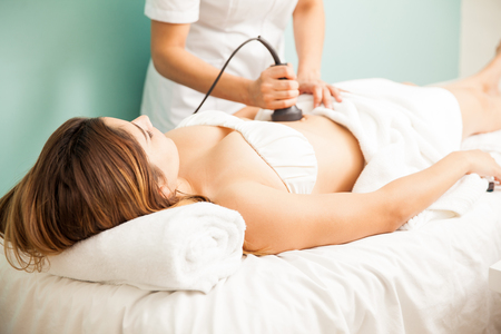 Female therapist giving a reductive and reaffirming treatment to a client and focusing on her belly