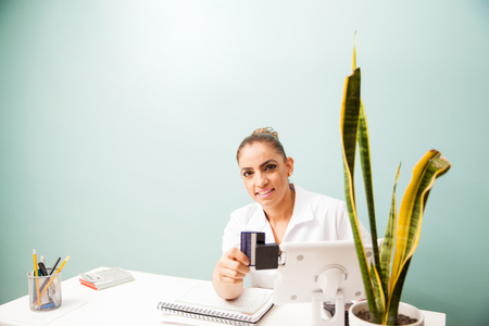 Portrait of a female cashier at a business front desk swiping a credit card in a reader and smiling