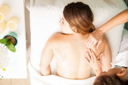 holistic view: Top view of a relaxed beautiful brunette getting a back massage at a health spa and relaxing