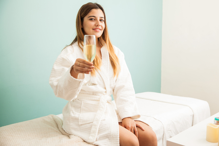 pampered: Gorgeous brunette in a robe drinking champagne and getting pampered in a hotel spa during her vacations