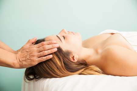 Profile view of a cute young woman getting her energy balanced at a reiki session in a health clinic and spa