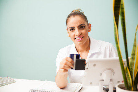 front desk: Therapist and business owner swiping a credit card and smiling while sitting in a front desk at a spa