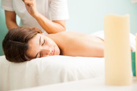 massages: Femme thérapeute donnant un massage lomi lomi à un client à un clininc de santé et spa
